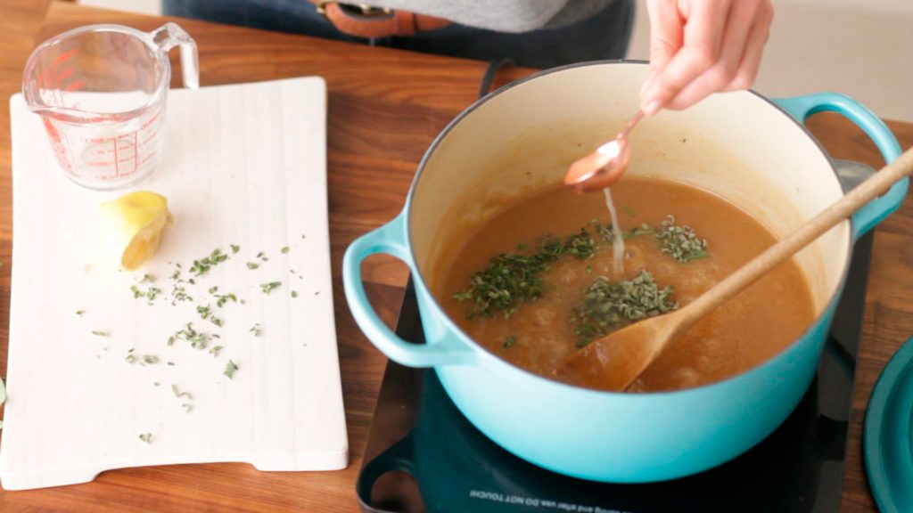 Gravy in a stockpot beside a cutting board and measuring cup