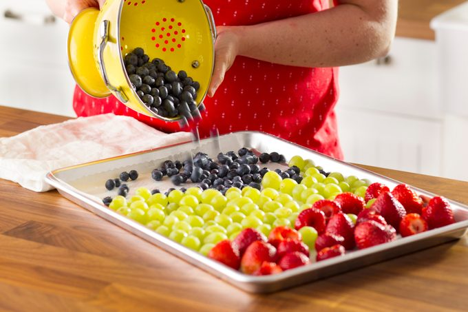 Blueberries being poured on a baking sheet along side grapes and strawberries from a strainer
