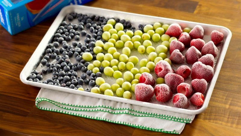 Frozen grapes, blueberries, and raspberries on a baking sheet