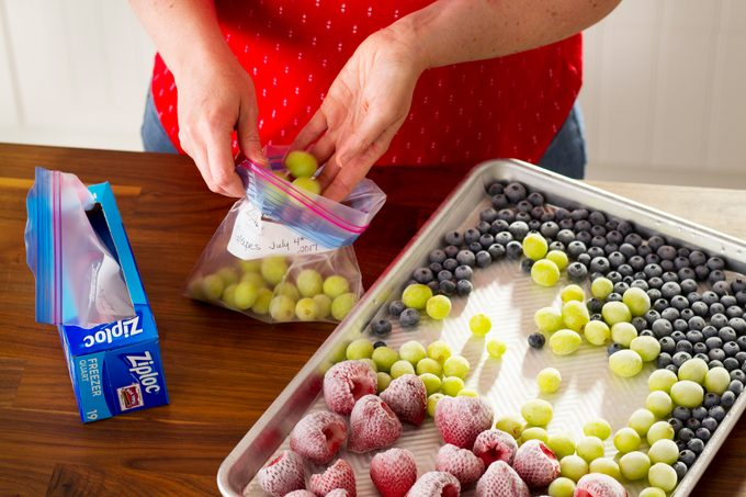 Frozen fruit is being carefully removed from a baking sheet and put into labelled plastic bags