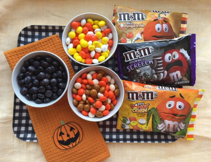Three bowls of fall M&Ms together beside their respective plastic bags