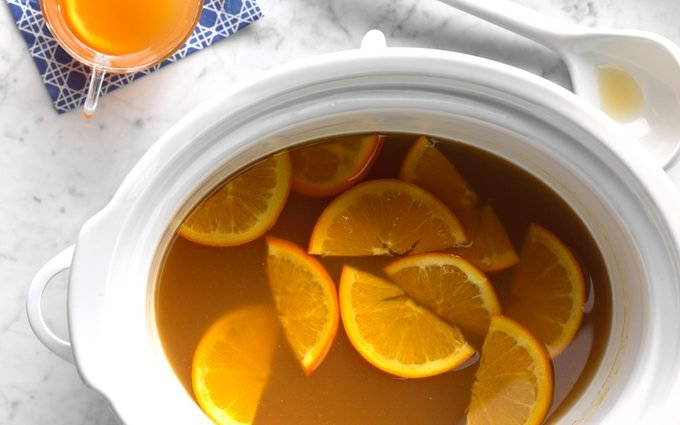 Slow cooker open with slices of oranges floating inside