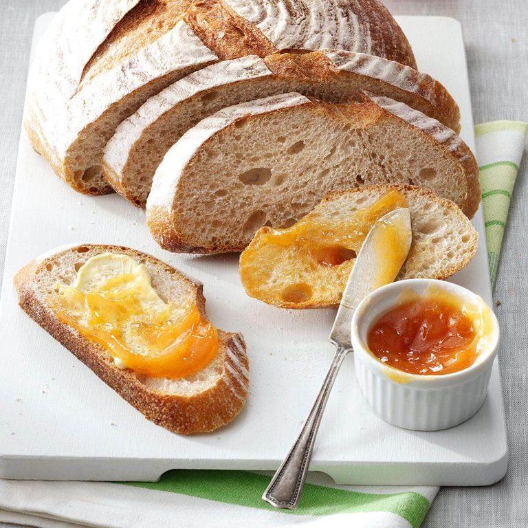 A cutting board with sliced bread and pretty peach jam