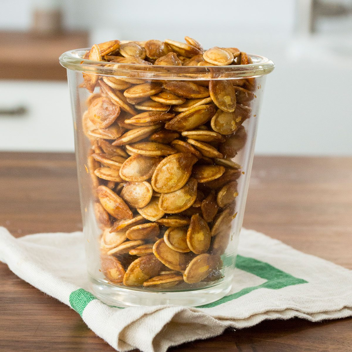 Cup of roasted pumpkin seeds on top of a green and white towel