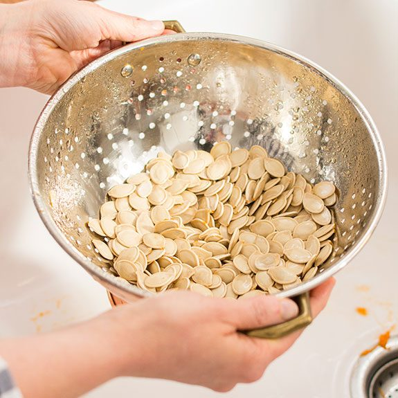 Rinsed pumpkin seeds in a strainer over a white sink
