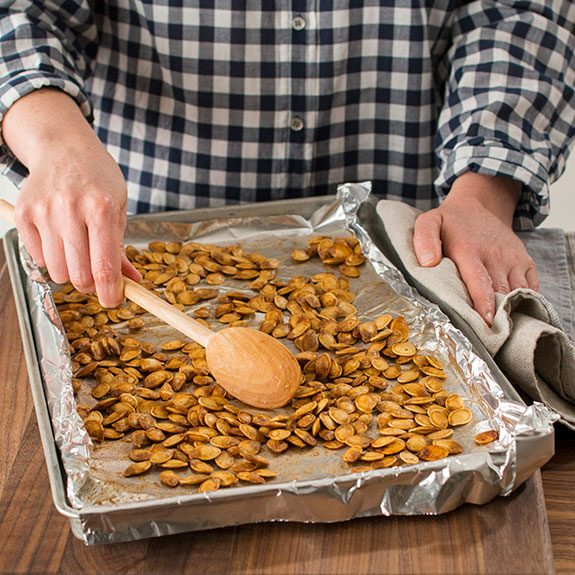 Person using a wooden spoon to stir perfectly roasted pumpkin seeds on a baking sheet lined with foil