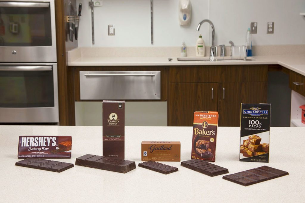 Line-up of different brands of baking chocolate in a kitchen