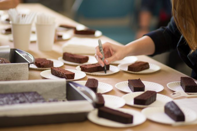 Thin slices of chocolate cake on unmarked white plates ready to be handed out