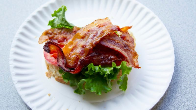 Bacon on top of a patty and lettuce in a burger
