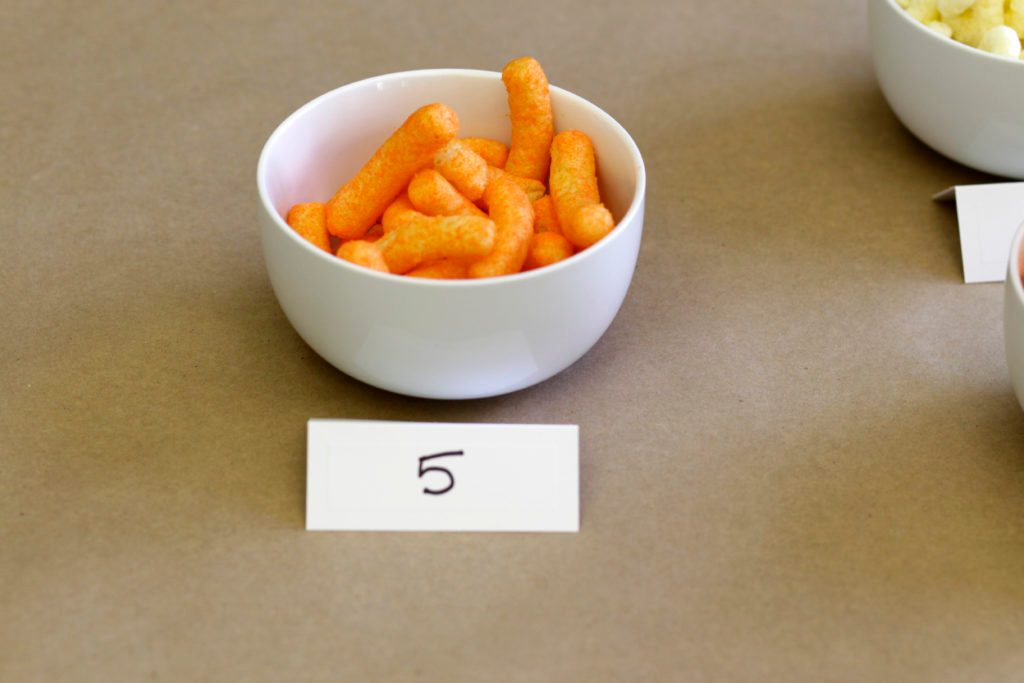 Bowl with the number 5 filled with cheese puffs