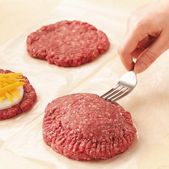 Using a fork, the edges of the combined patties are being sealed
