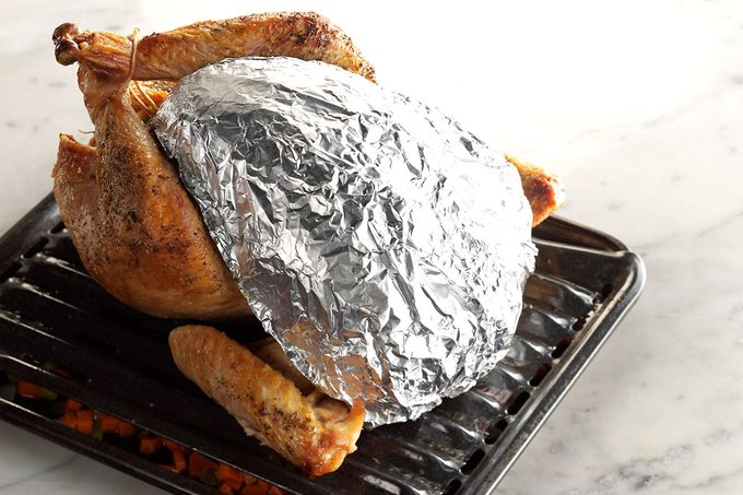 Turkey on a rack with its middle wrapped in foil