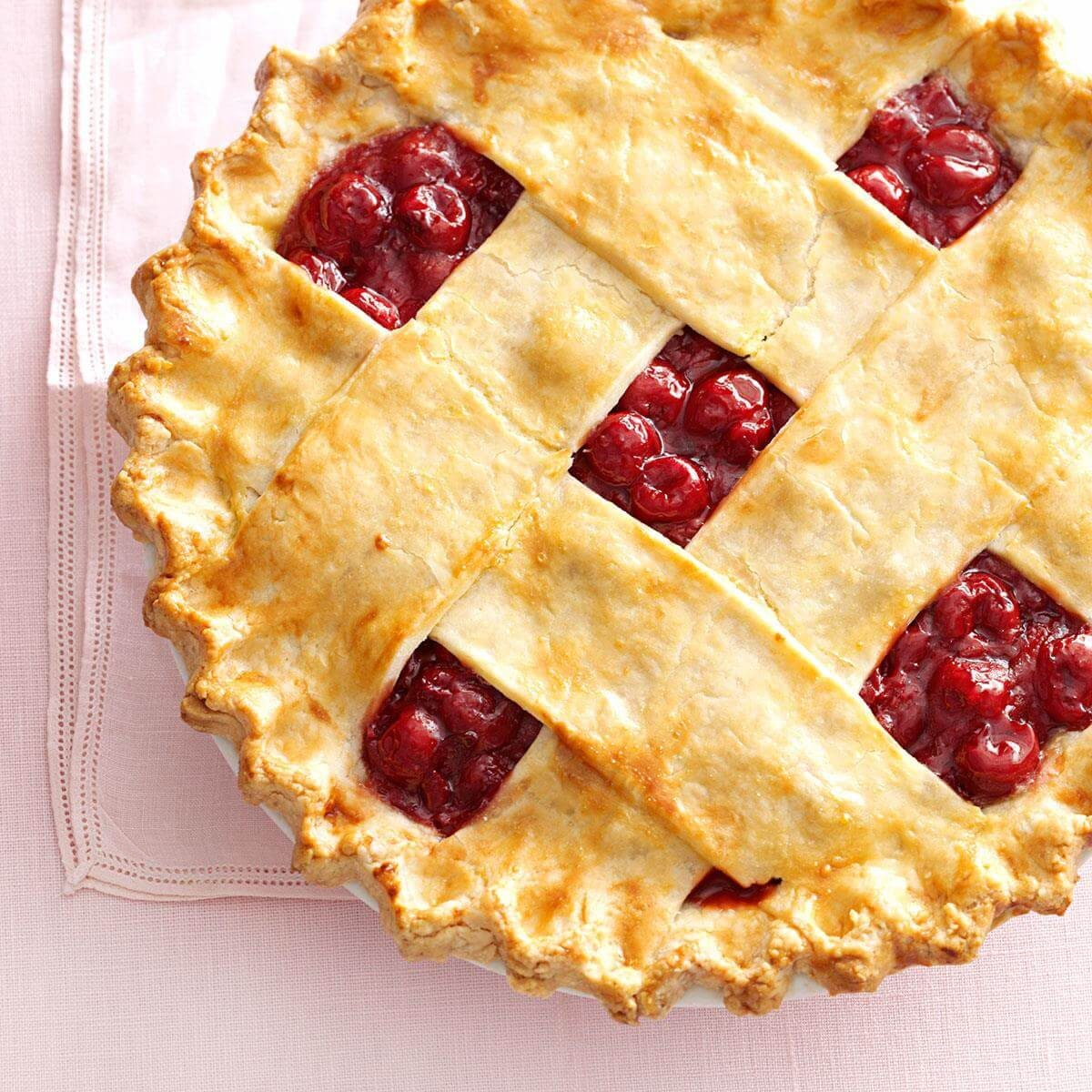 Tart Cherry Lattice Pie on a pink tablecloth.