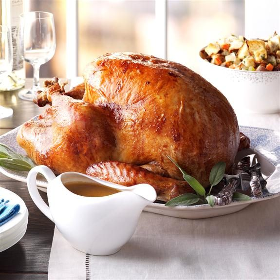 Whole cooked turkey on a platter beside a gravy boat and other sides