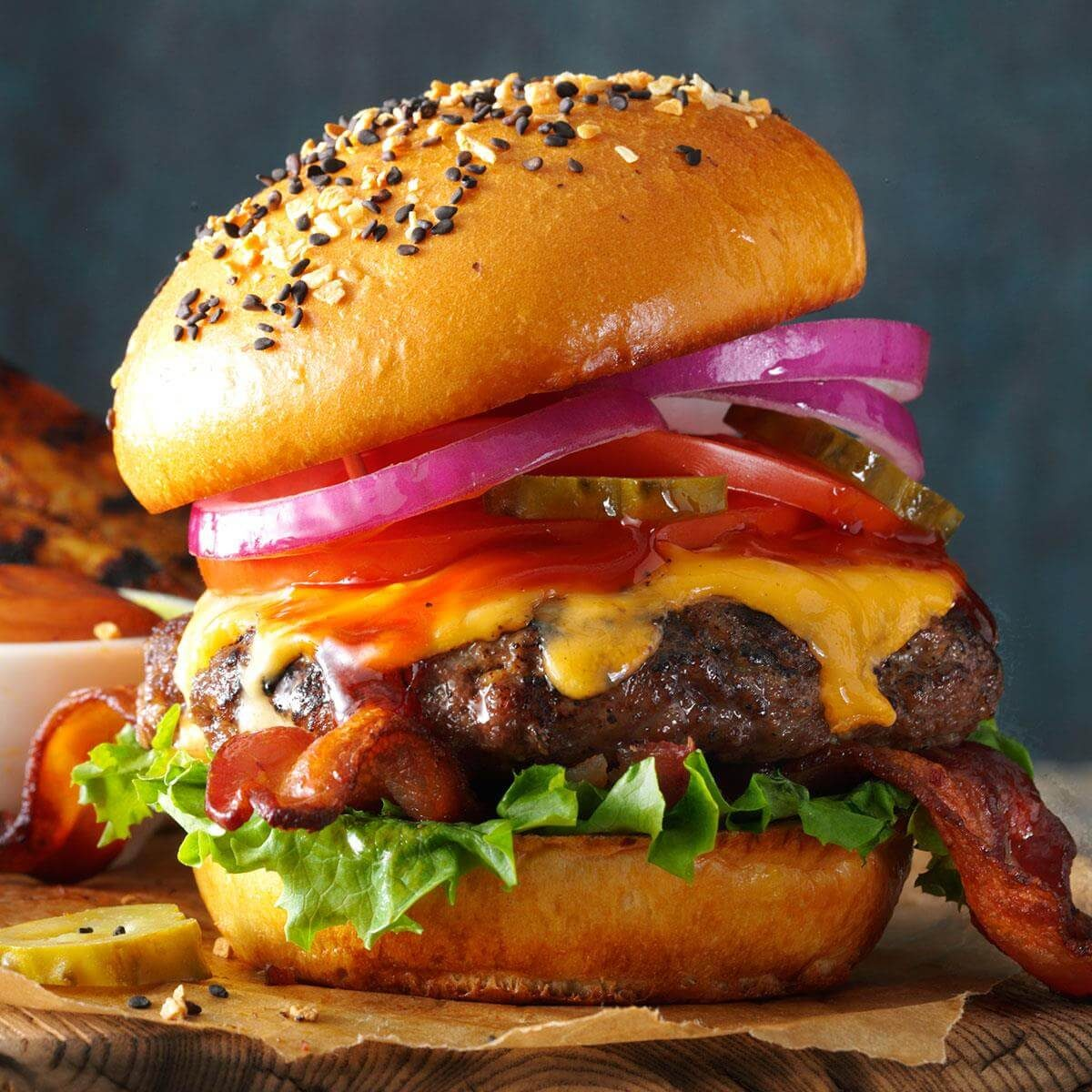 Grilling the perfect burger piled high with cheese, tomatoes, onions, pickles, bacon, lettuce and a side of steak fries