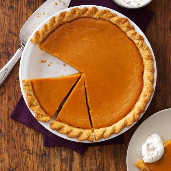 Pumpkin pie with one slice missing and two more cut and ready to eat