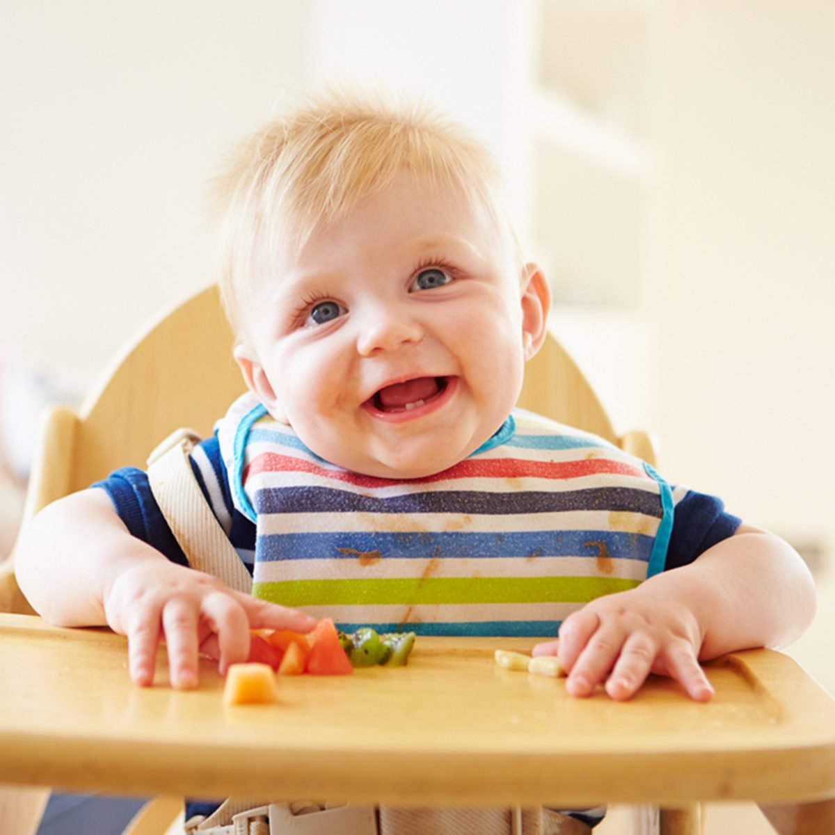 Baby Boy Eating Finger Fods In High Chair