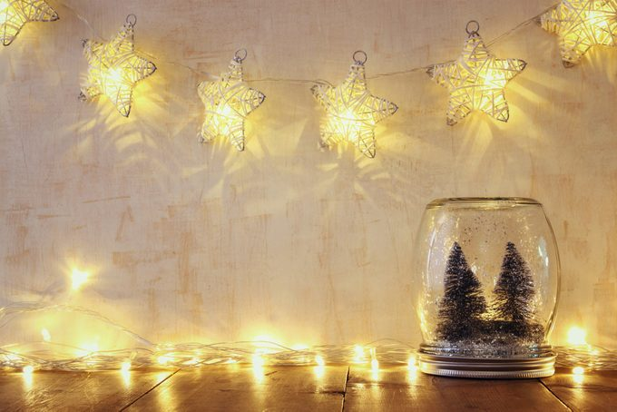 Low key and vintage filtered image of christmas trees in mason jar with garland warm lights.