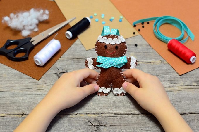 Child holding a felt gingerbread man in his hands.