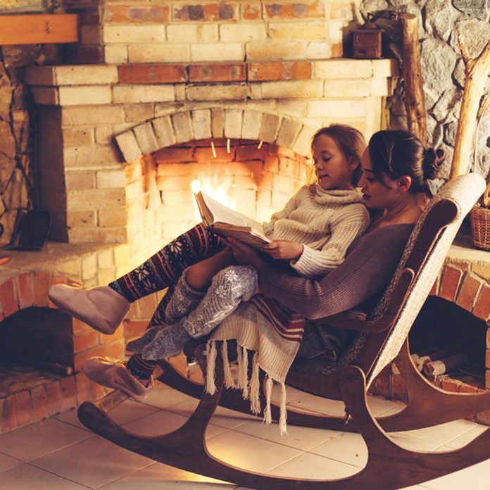 Mom with child reading book and relaxing by the fire place some cold evening, winter weekends, cozy scene; Shutterstock ID 547799722; Job (TFH, TOH, RD, BNB, CWM, CM): TOH