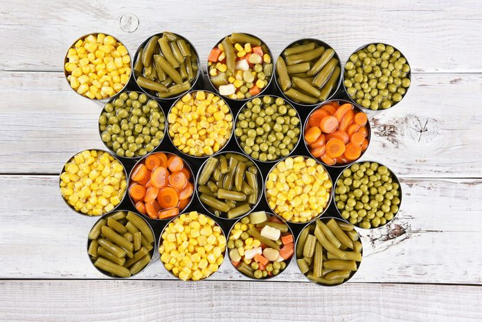 High angle shot of a group of canned vegetables on a rustic white wood table.