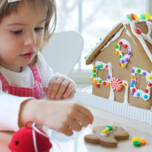 Little girl decorating gingerbread house for Christmas