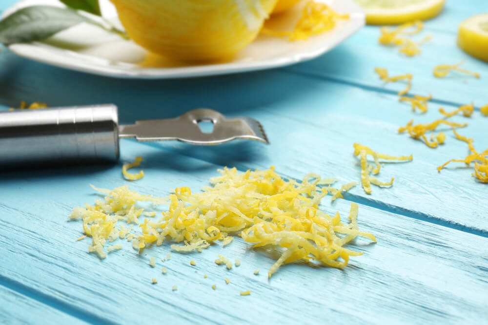 Lemon zest and special tool on wooden table