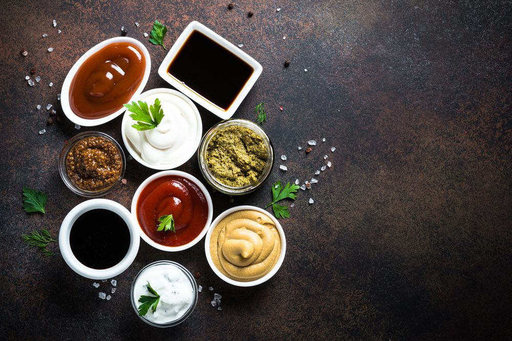 Set of sauces - ketchup, mayonnaise, mustard soy sauce, bbq sauce, pesto, mustard grains and pomegranate sauce on dark rusty stone or metal background