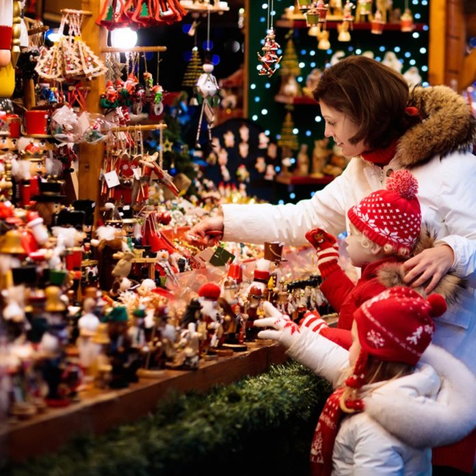 Mother and child in warm hat watching handmade glass Christmas tree ornaments at traditional German Xmas street market. Family with child shopping for Christmas presents on winter fair on snowy day.; Shutterstock ID 736421758; Job (TFH, TOH, RD, BNB, CWM, CM): TOH