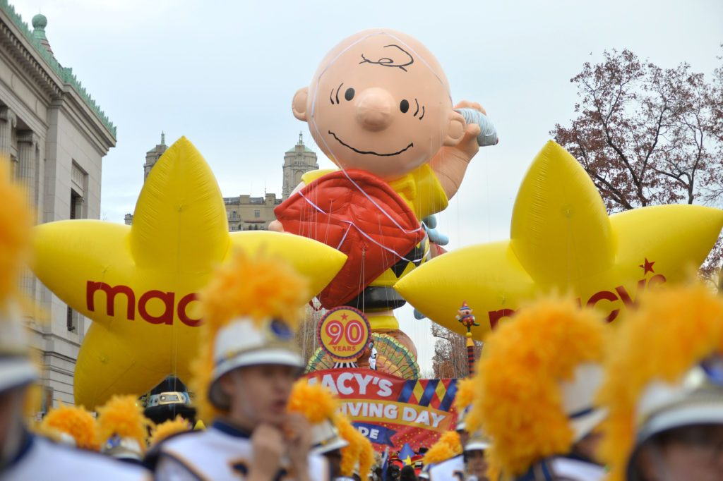 Marching bands and the Charlie Brown balloon at the start of the Macys Thanksgiving Day parade.