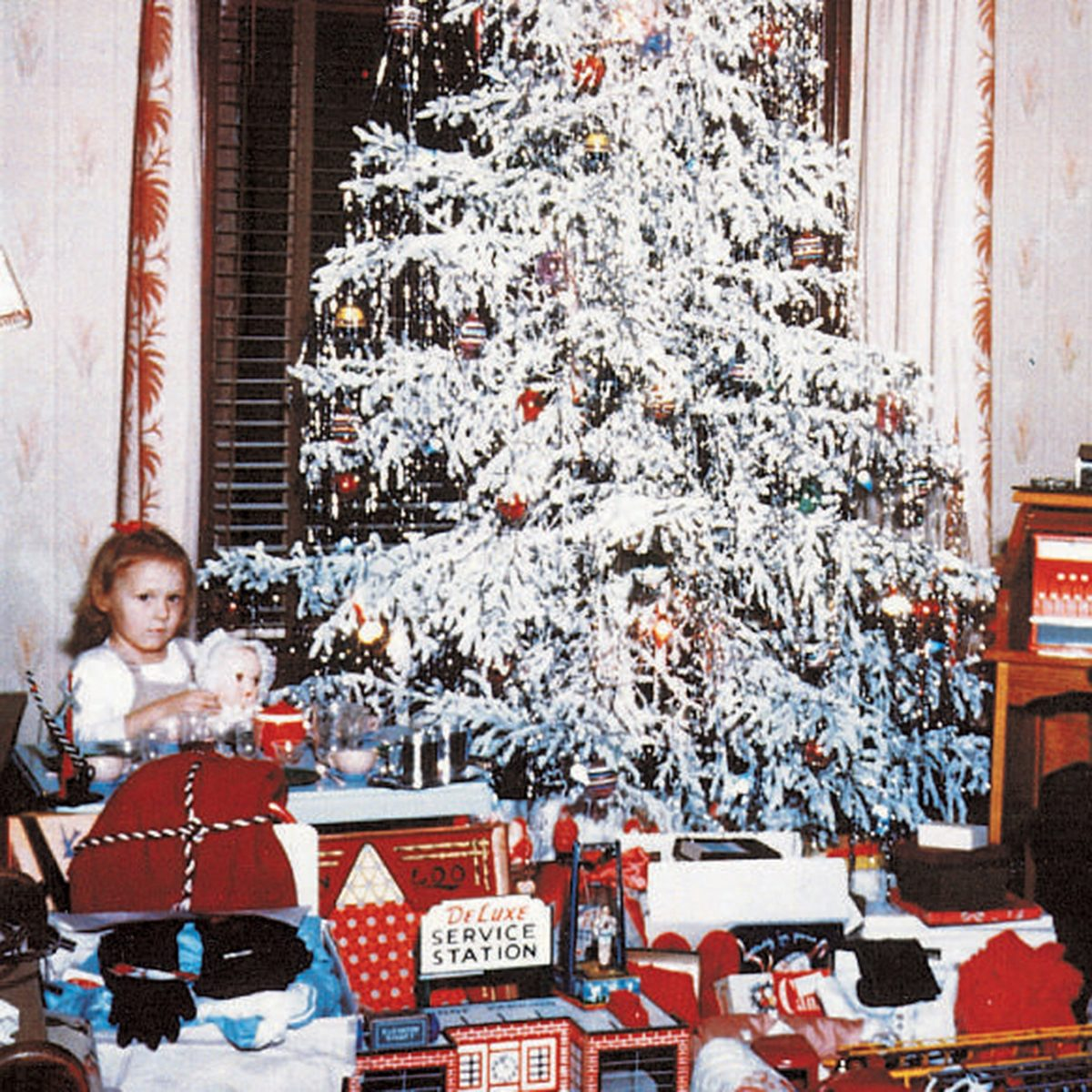 5a1f5ff5b230 Girl and a boy sitting among opened presents under a Christmas tree