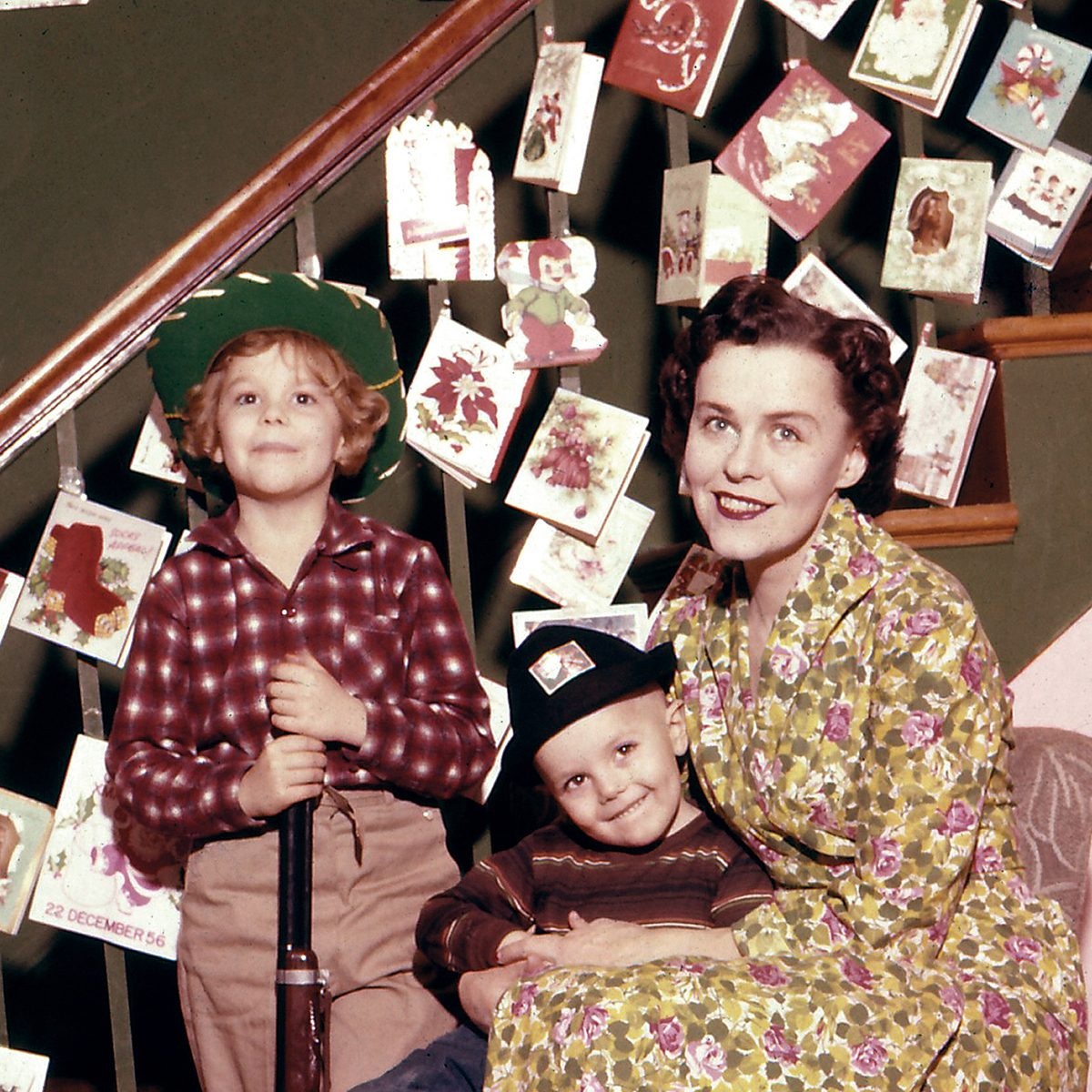 Mother with two sons in front of a decorated staircase