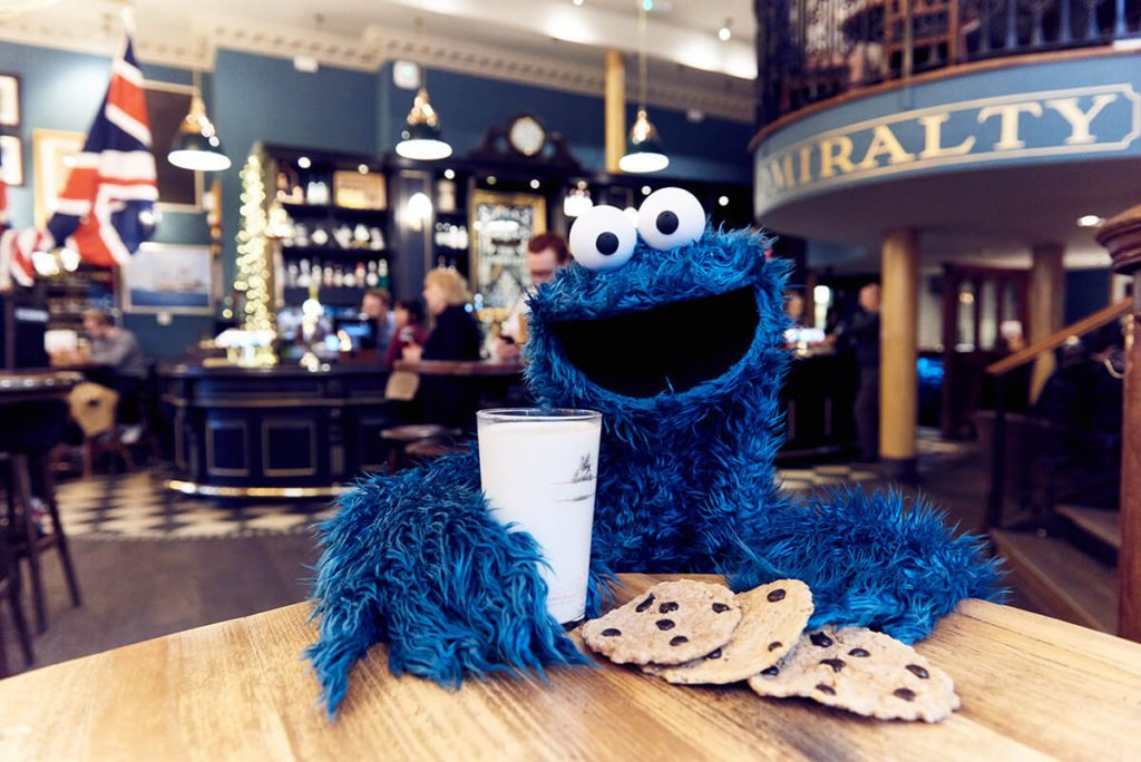Cookie Monster enjoying a pint of milk in a pub.