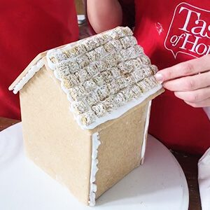 Person with a red apron constructing a gingerbread house