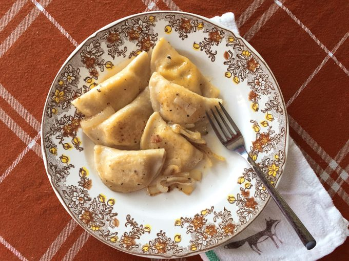 Pierogi on a decorative plate with a metal fork