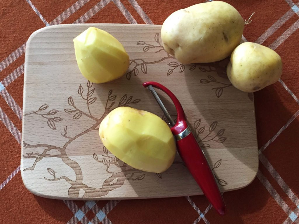 Potatoes being peeled on a wooden cutting board
