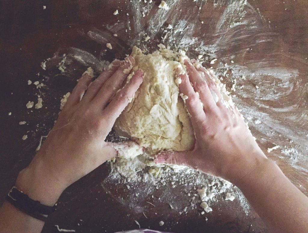Person kneading dough on a floured surface
