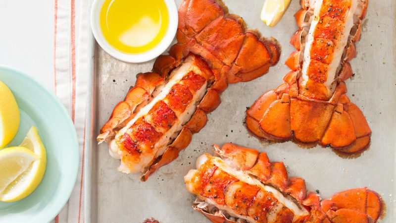 Lobster tails on a baking sheet with butter and lemon wedges