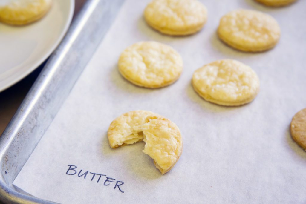Baking sheet labelling cookie-shaped pieces of pie crust as being made with butter
