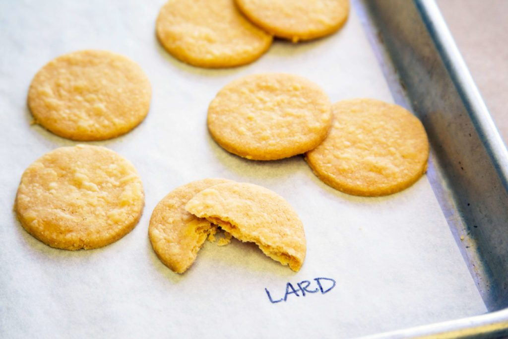 Baking sheet labelling cookie-shaped pieces of pie crust as being made with lard