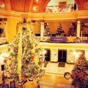 Decorate inside of a building with multiple Christmas trees