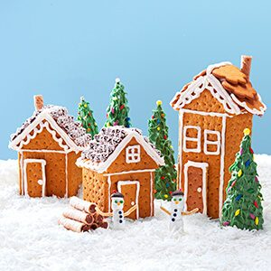 Three gingerbread houses on a snowy field