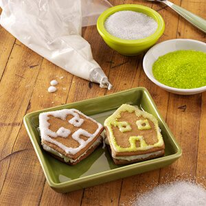 Gingerbread house sandwich cookies on a plate