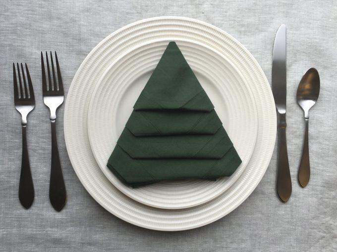 Green napkin folded like a Christmas tree