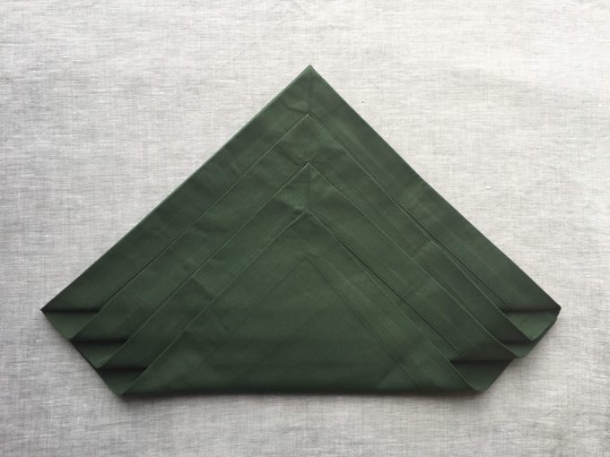 Green napkin with several more similar folds in it