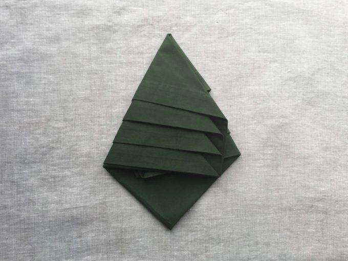 Green napkin beginning to take on a tree shape