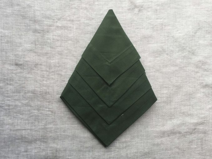 Green napkin flipped again and taking on a tree shape