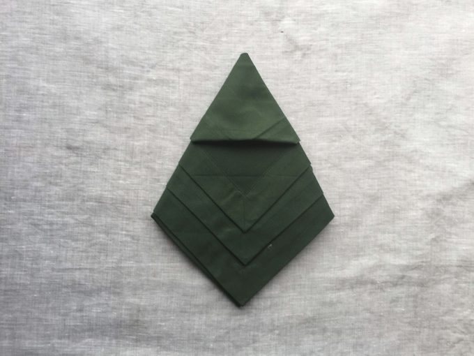 Tucking in the layers of the green napkin to make the tree