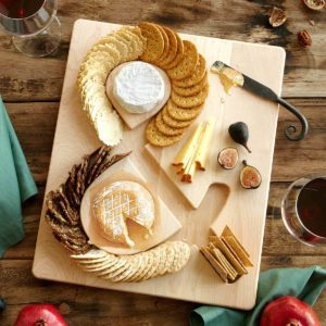 Crackers arranged in an infinity sign on a cutting board with cheese