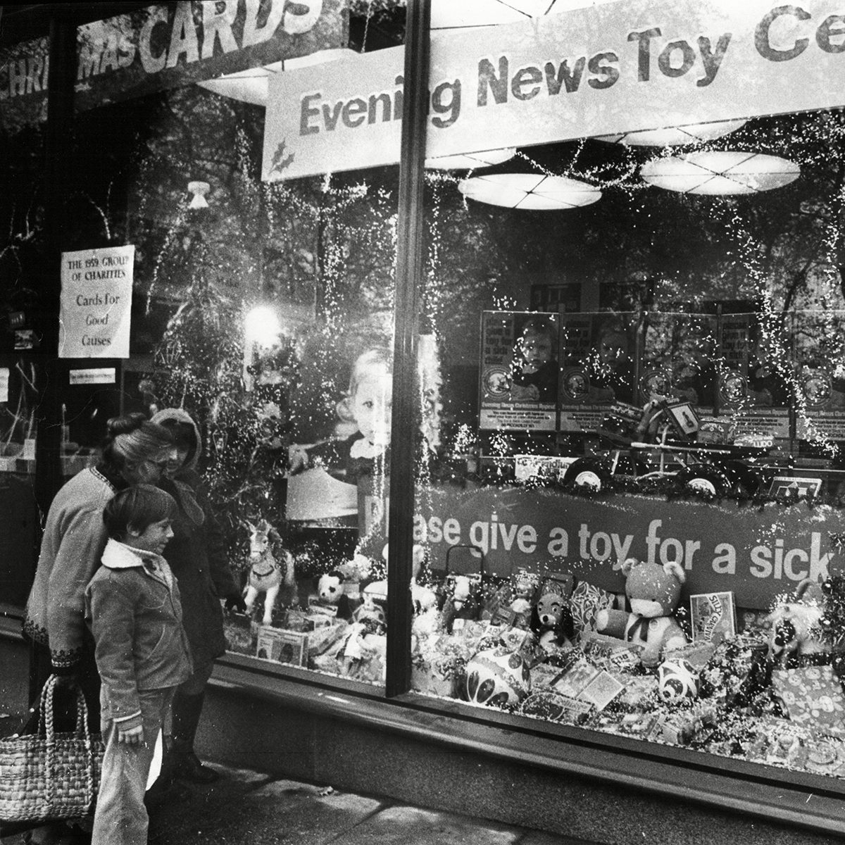 Shoppers Look In Store Window Display For Evening News's Toy For A Sick Child Campaign 1973.